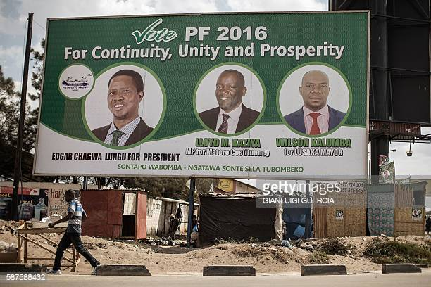 People walk by a billboard with picture of the incumbent president Edgar Lungu of the Patriotic Front ruling Party two days ahead of Zambian...