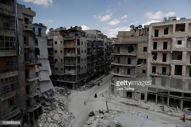 People walk by a building in the Sha'ar neighbourhood of Aleppo Syria which was destroyed by a barrel bomb on June 3 2014 Fifteen people died in the...