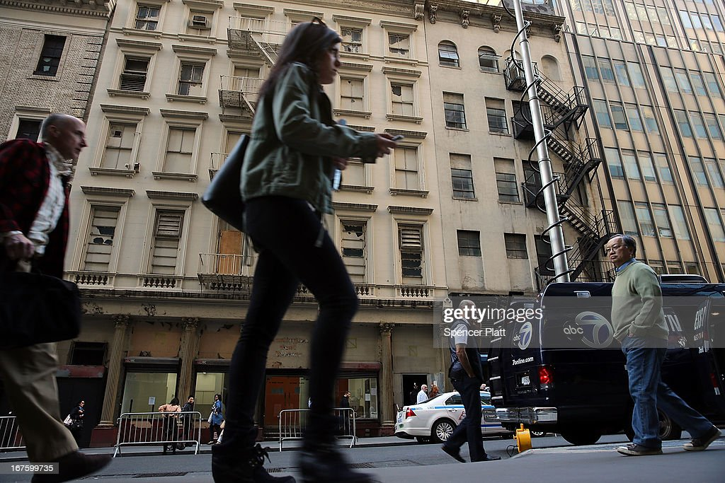 People walk by a building on Park Place in lower Manhattan where a piece of landing gear believed to be from one of the planes destroyed in the September 11 attacks has been discovered on April 26, 2013 in New York City. The landing gear was discovered wedged between a mosque site and a building blocks from the World Trade Center site.