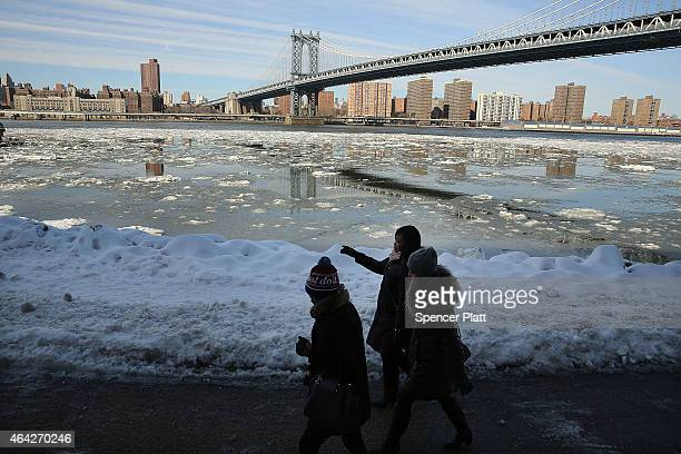 People walk by a buildup of ice in the East River near the Manhattan Bridge on February 23 2015 in New York City New York City and much of the East...