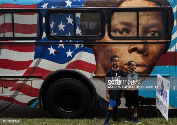 TOPSHOT People walk by a bus with a mural of US abolitionist and former slave Harriet Tubman on it as they arrive to attend the public viewing for...