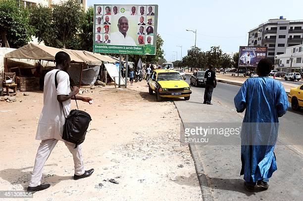 People walk by a campaign poster for incumbent Dakar Mayor Khalifa Sall in a street of Dakar Senegal on June 26 2014 Senegalese will vote on June 29...