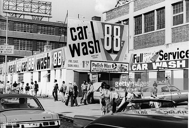 People walk by a car wash in New York City New York circa 1970