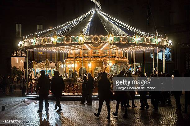 people walk by a carousel adorned with christmas lighting and decorations in piazza navona on december