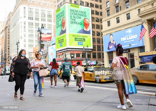 People walk by a CDC billboard encouraging people to wear a face masks outside Madison Square Garden as the city continues Phase 4 of reopening...
