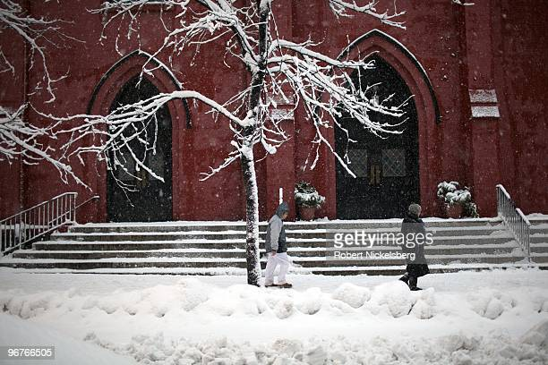 People walk by a church during a winter snowstorm February 10 2010 in Brooklyn New York The storm described as a northeaster covered the midAtlantic...