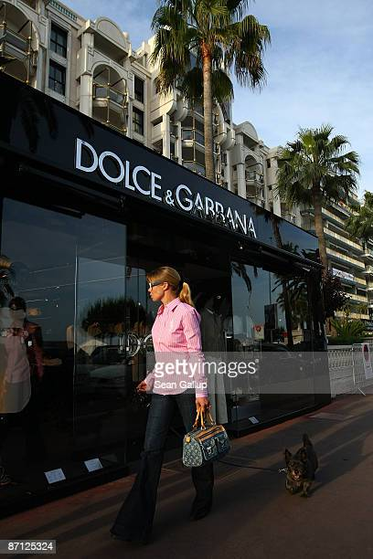People walk by a Dolce and Gabbana luxury clothing store on Boulevard de la Croisette the main drag near the Cannes International Film Festival on...