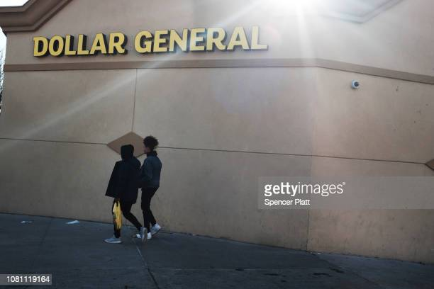 People walk by a Dollar General store on December 11 2018 in the Brooklyn borough of New York City As the income gap between rich and poor continues...