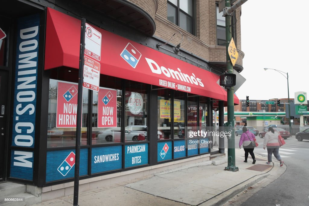 People walk by a Domino's restaurant on October 12, 2017 in Chicago, Illinois. Shares of the restaurant chain fell 4 percent today despite reporting an increase of more than 8 percent in domestic same-store sales.