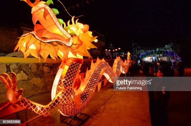 People walk by a dragon lantern in a lantern show made by villagers for the upcoming Lantern Festival in Zhangjiazhuang village in Shexian county in...