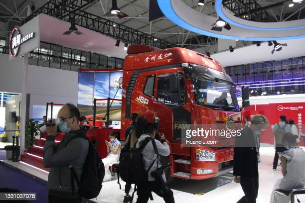 People walk by a FAW J6P dump truck during China International Big Data Industry Expo at Guiyang International Conference and Exhibition Center on...