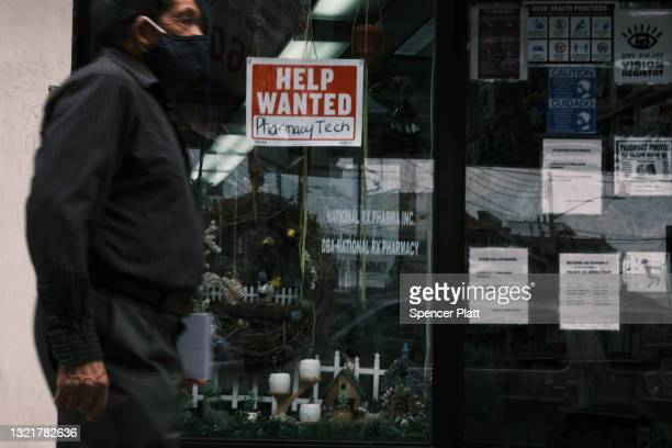 People walk by a Help Wanted sign in the Queens borough of New York City on June 04, 2021 in New York City. The U.S. Economy added 559,000 jobs in...