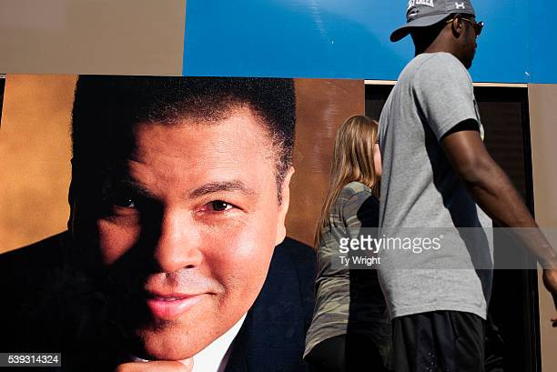 People walk by a large picture of Muhammad Ali at the Muhammad Ali Center on June 10 2016 in Louisville Kentucky After the funeral and the eulogy...