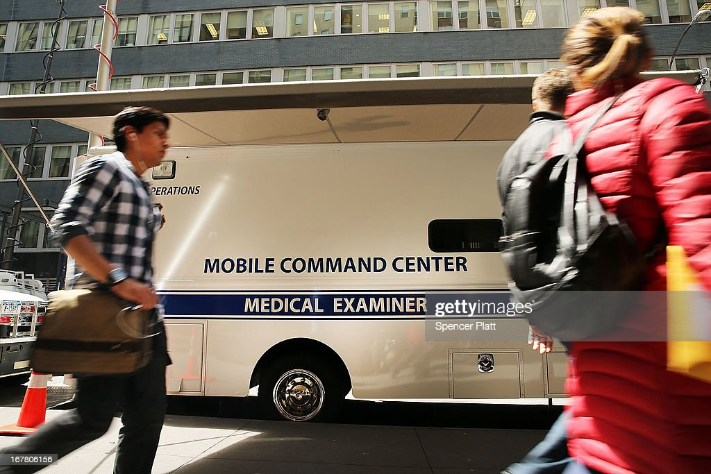 People walk by a Mobile Command Center for the Medical Examiners outside of a building on Park Place in lower Manhattan where a piece of one of the planes destroyed in the September 11 attacks has been discovered on April 30, 2013 in New York City. The Medical Examiners office is searching the area for human remains.The part of the plane, a support structure from a trailing edge flap found on the wing of a Boeing 767, was discovered wedged between a mosque site and luxury high-rise apartment building, about three blocks north from the World Trade Center site.