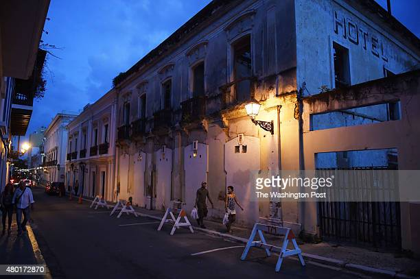 People walk by a near shell of a building on Friday July 03 2015 in Old San Juan Puerto Rico The historic area brings in many tourists