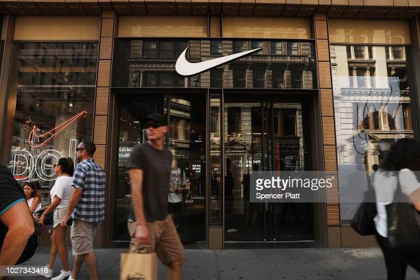People walk by a Nike store in Manhattan on September 5 2018 in New York New York A new ÒJust Do ItÓ TV commercial by Nike Inc will be narrated by...