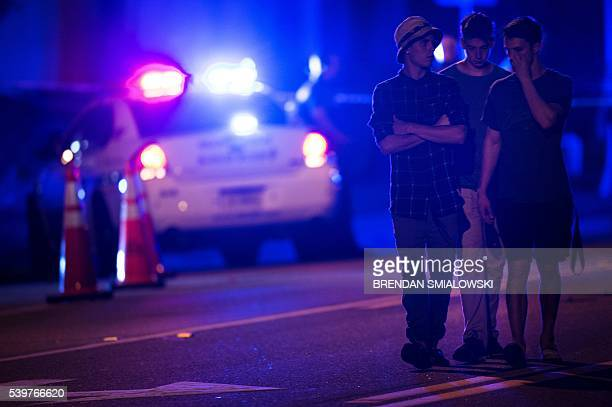 People walk by a police roadblock near the Pulse nightclub on June 12 2016 in Orlando Florida People close to the gunman behind the attack on a gay...