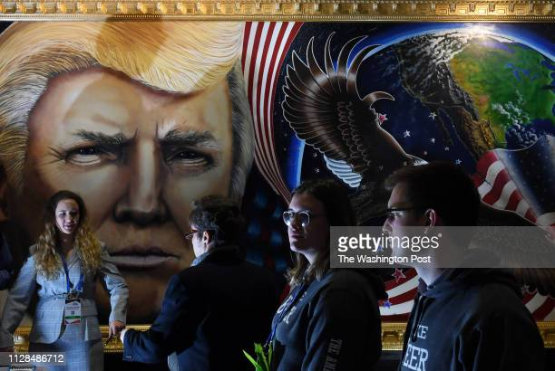 People walk by a portrait of President Donald Trump that was completed by artist Julian Raven at the Conservative Political Action Conference or CPAC...