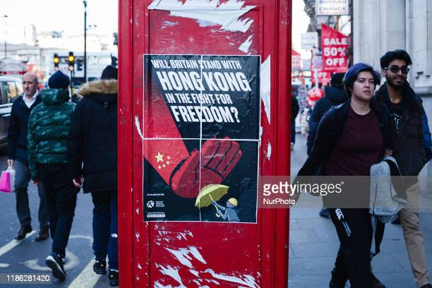 People walk by a poster calling for British solidarity with prodemocracy protesters in Hong Kong put up by the 'Fight For Freedom Stand With Hong...