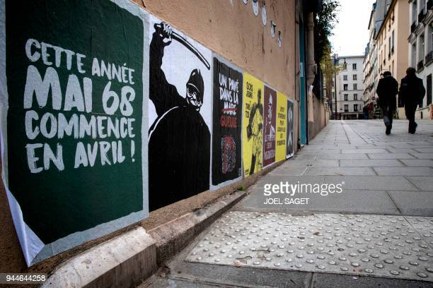 People walk by a poster reading ' This year May 68 begins in April' in reference to the civil unrest in France during May 1968 in Paris on April 11...