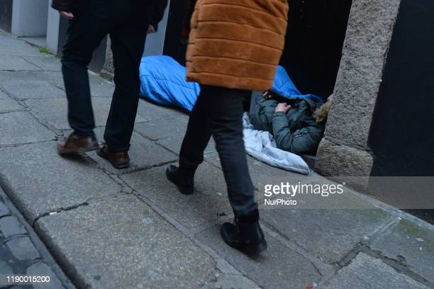 People walk by a rough sleeper in a busy preChristmas Dublin's Temple Bar On Saturday December 21 in Dublin Ireland