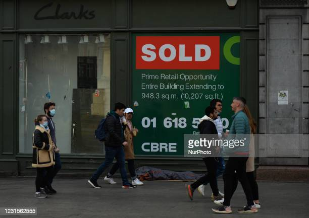 People walk by a rough sleeper outside a closed Clarks shop in Dublin city center during Level 5 Covid-19 lockdown. On Saturday, 6 March in Dublin,...