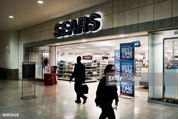 People walk by a Sears store in a nearly empty Westfield Meriden shopping mall on March 28 2017 in Meriden Connecticut As consumers buying habits...