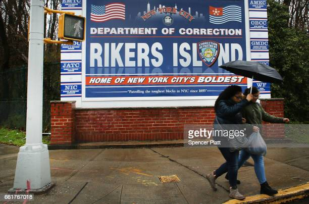 People walk by a sign at the entrance to Rikers Island on March 31 2017 in New York City New York Mayor Bill de Blasio has said that he agrees with...