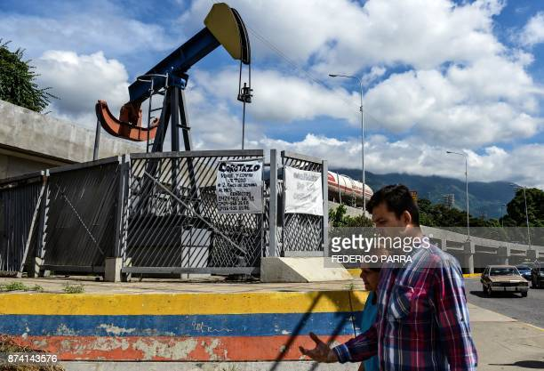 People walk by a small square with an oil pump in one of the access roads to the Central University of Venezuela in Caracas on November 14 2017...