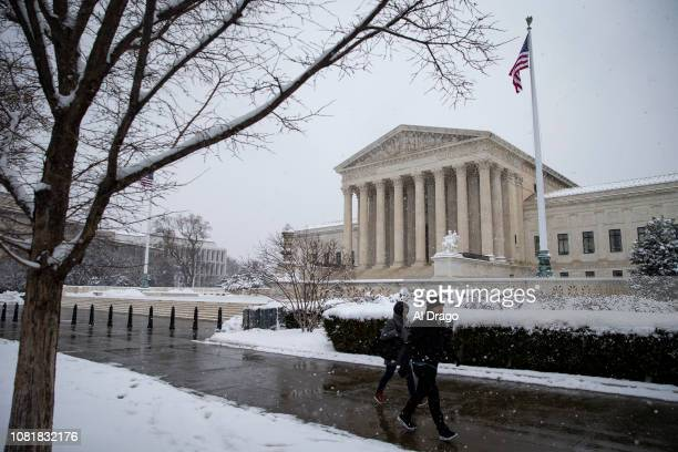 People walk by a snow covered Supreme Court on January 13 2019 in Washington DC The DC area was hit with 47 inches of snow accumulation with the...