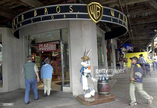 People walk by a statue of cartoon character Bugs Bunny dressed as a fisherman outside of a Warner Bros Studio Store July 9 2001 on Pier 39 in San...