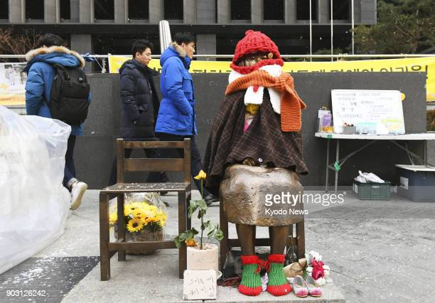 """People walk by a statue symbolizing so-called """"comfort women"""" in front of the Japanese Embassy in Seoul on Jan. 9, 2018. Tokyo and Seoul have been at..."""