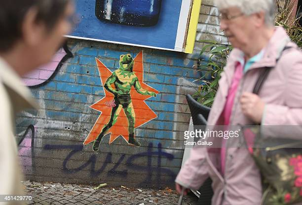 People walk by a street artist's version of Kermit the Frog in Oppelner Strasse in Kreuzberg district on June 26 2014 in Berlin Germany Berlin with...