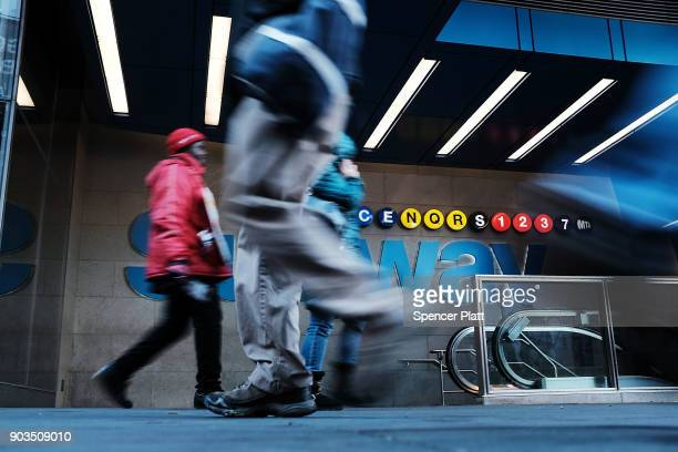 People walk by a subway station on January 10 2018 in New York City The New York City subway system which opened in 1904 and is the world's largest...