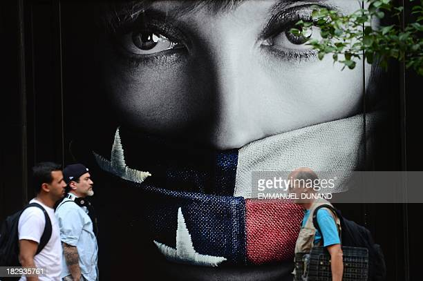 People walk by a television series advertisement featuring actress Toni Colette gagged by a US flag in New York on October 2 2013 Government...