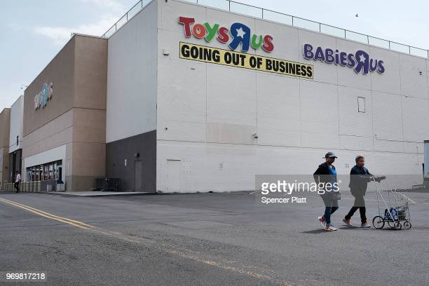 People walk by a Toys R Us store in Brooklyn on June 8 2018 in New York City All 735 Toys R Us stores in America are set to close by the end of June...