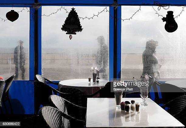 People walk by a traditional Russian restaurant on the boardwalk in Brighton Beach one of the largest Russian speaking enclaves in the Western...