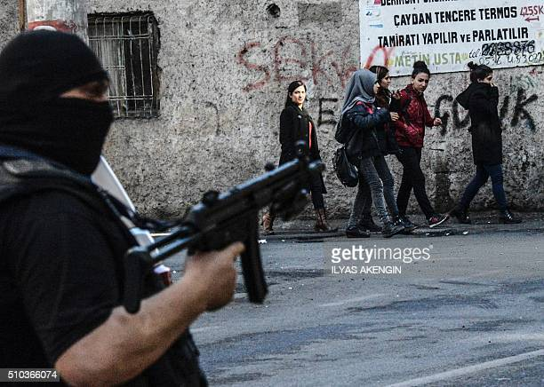 TOPSHOT People walk by a Turkish police officer holding an assault riffle during clashes with protestors demonstrating against government imposed...