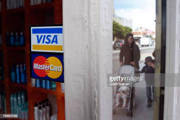 People walk by a window sticker advertising Visa and MasterCard credit cards February 25 2008 in San Francisco California Visa Inc is hoping that its...