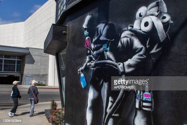 TOPSHOT People walk by an apocalyptic mural by Hijackhart where soldiers wearing face masks fight Covid19 with disinfectant and hand sanitizers...