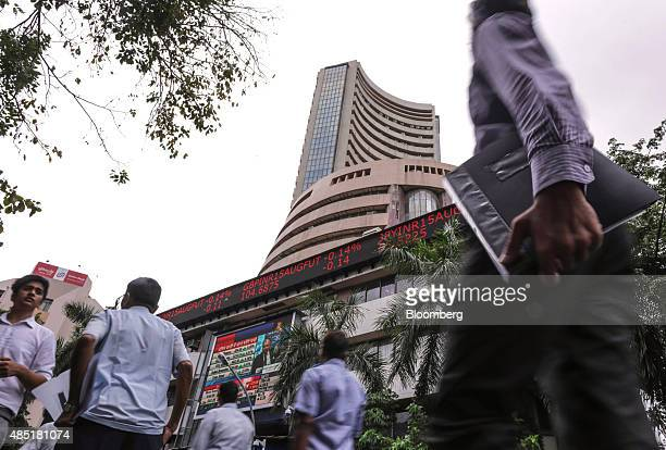 People walk by an electronic ticker board that indicates stock figures at the Bombay Stock Exchange in Mumbai India on Tuesday Aug 25 2015 Indian...