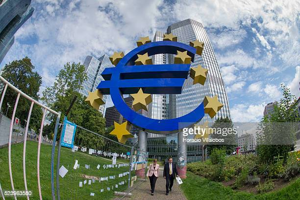 People walk by an installation near the Euro symbol in front of European Central Bank Headquarters in Willy Brandt Platz Frankfurt Germany 07 August...