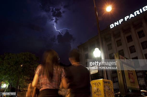 People walk by an office of French bank BNPParibas as lightning strikes during a thunderstorm over the city on June 8 2014 in Paris AFP PHOTO / PABLO...
