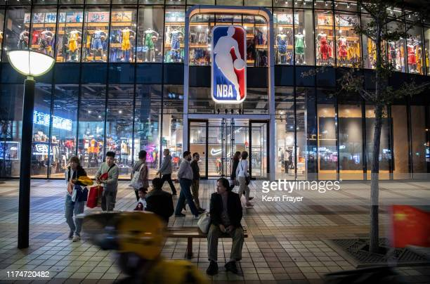 People walk by and sit outside the NBA flagship retail store on October 9 2019 in Beijing China The NBA is trying to salvage its brand in China amid...