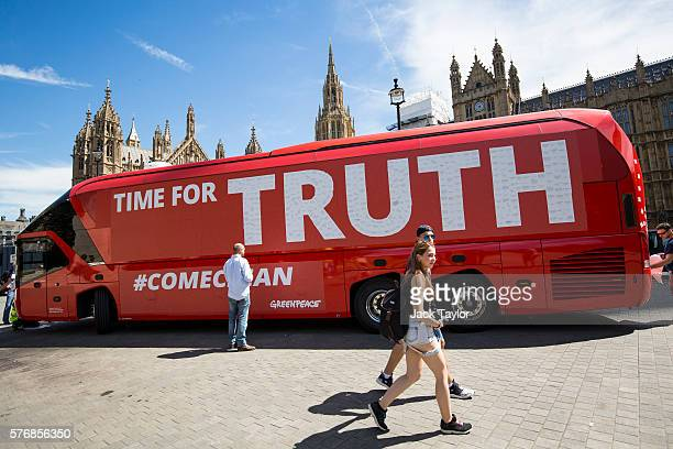 People walk by as a 'Vote Leave' battle bus is rebranded outside the Houses of Parliament in Westminster by the environmental campaign group...