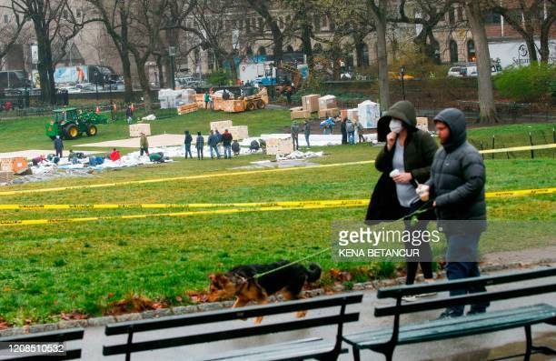 People walk by Central Park as workers set up a field hospital in front of Mount Sinai West Hospital on March 29 2020 in New York City A senior US...