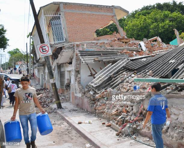 People walk by collapsed houses on Sept 21 2017 on a street in Jojutla in the state of Morelos near the epicenter of a magnitude 71 earthquake that...