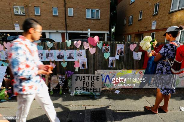 TOPSHOT People walk by floral and written tributes and missing person posters in the aftermath of the June 14 Grenfell Tower block fire in Kensington...