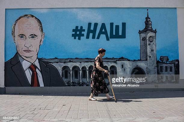People walk by fresh graffiti depicting Vladimir Putin in Simferopol on August 17 2015 in Simferopol Crimea Russian President Vladimir Putin signed a...