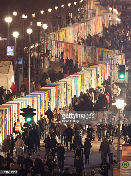 People walk by giant painted styrofoam dominoes standing near the Brandenburg Gate on November 7 2009 in Berlin Germany The over 1000 dominoes which...
